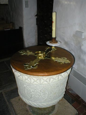 A fine round white stone font with a brass bound wooden cover