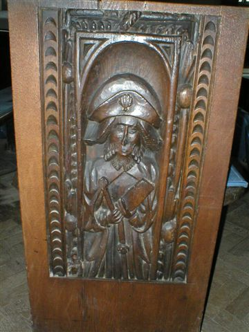 A pew end with a carving of a man weraing a bicorn hat